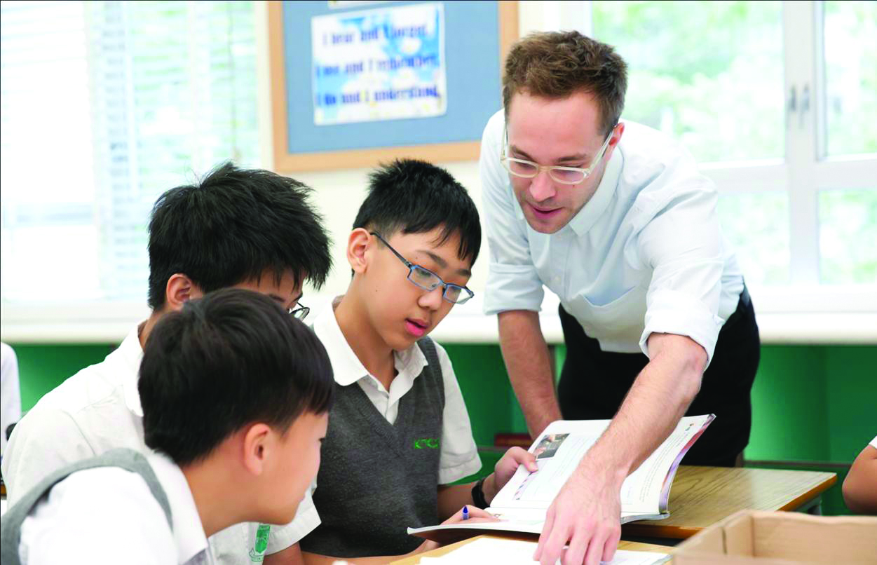 A TEFL teacher helping high school students with the task in English